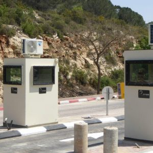 2 armored (bullet resistant booths) gurad booths on both sides of a road