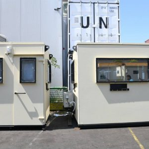Two guard shacks with bullet resistant windows and doors near UN containers